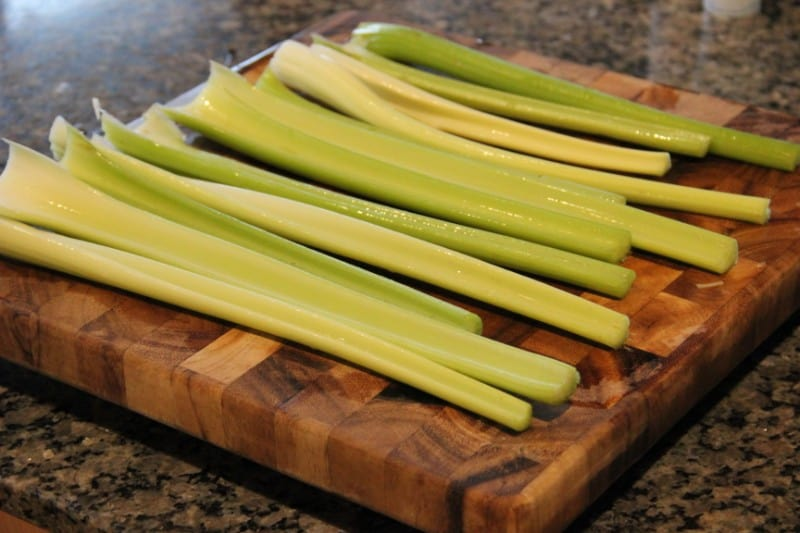 cleaned celery on a wooden cutting board