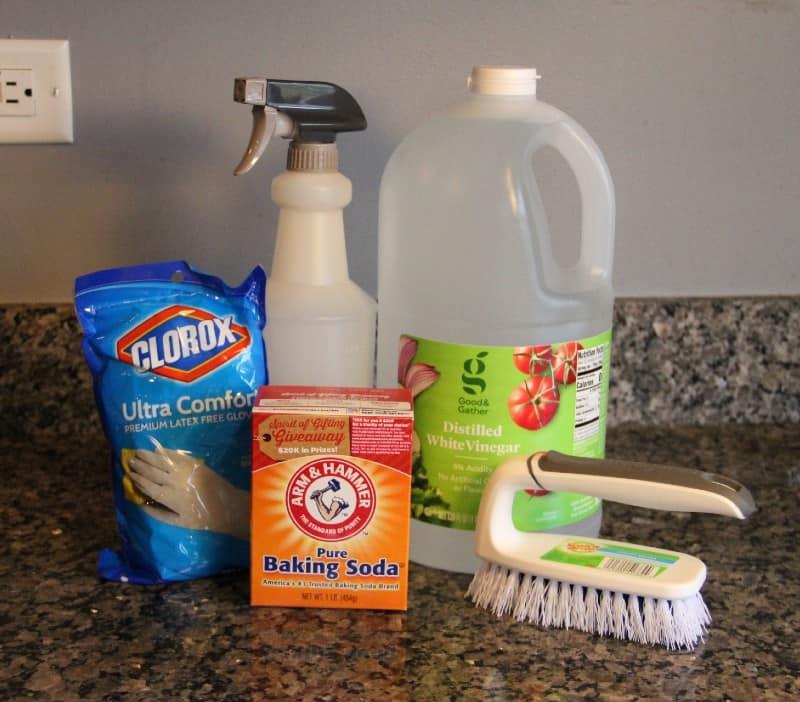 gloves, a spray bottle, baking soda, white vinegar, and a scrub brush on a counter top
