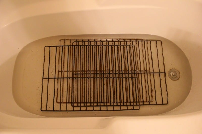 bath tub with oven racks and water in it