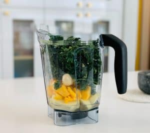 blender with fruit and greens