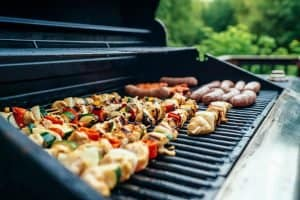 kebabs and sausages on a gas grill