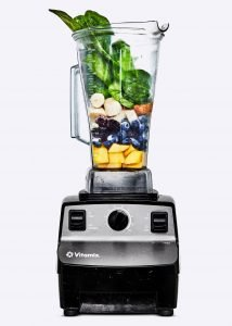 Vitamix with fruits and vegetables in it